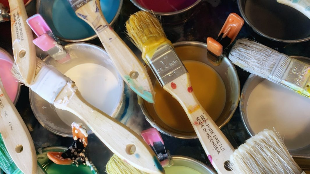 Top-down view of pots of encaustic paint with brushes resting on top of the metal pots.