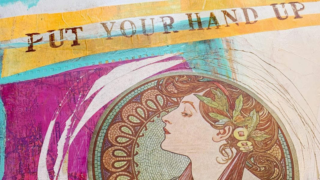 """Oblique angle of a mixed media painting featuring white, magenta, orange, and turquoise. There is a bohemian collage of a woman's head. The words, """"Put Your Hand Up"""" is stamped in sepia ink across the top."""