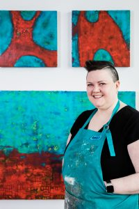 Amelia Kraemer is standing in a teal coloured apron in front of three turquoise and red paintings.