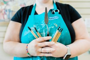 Amelia is wearing a black t-shirt and teal coloured apron. She is holding four scraping tools and a palette knife.