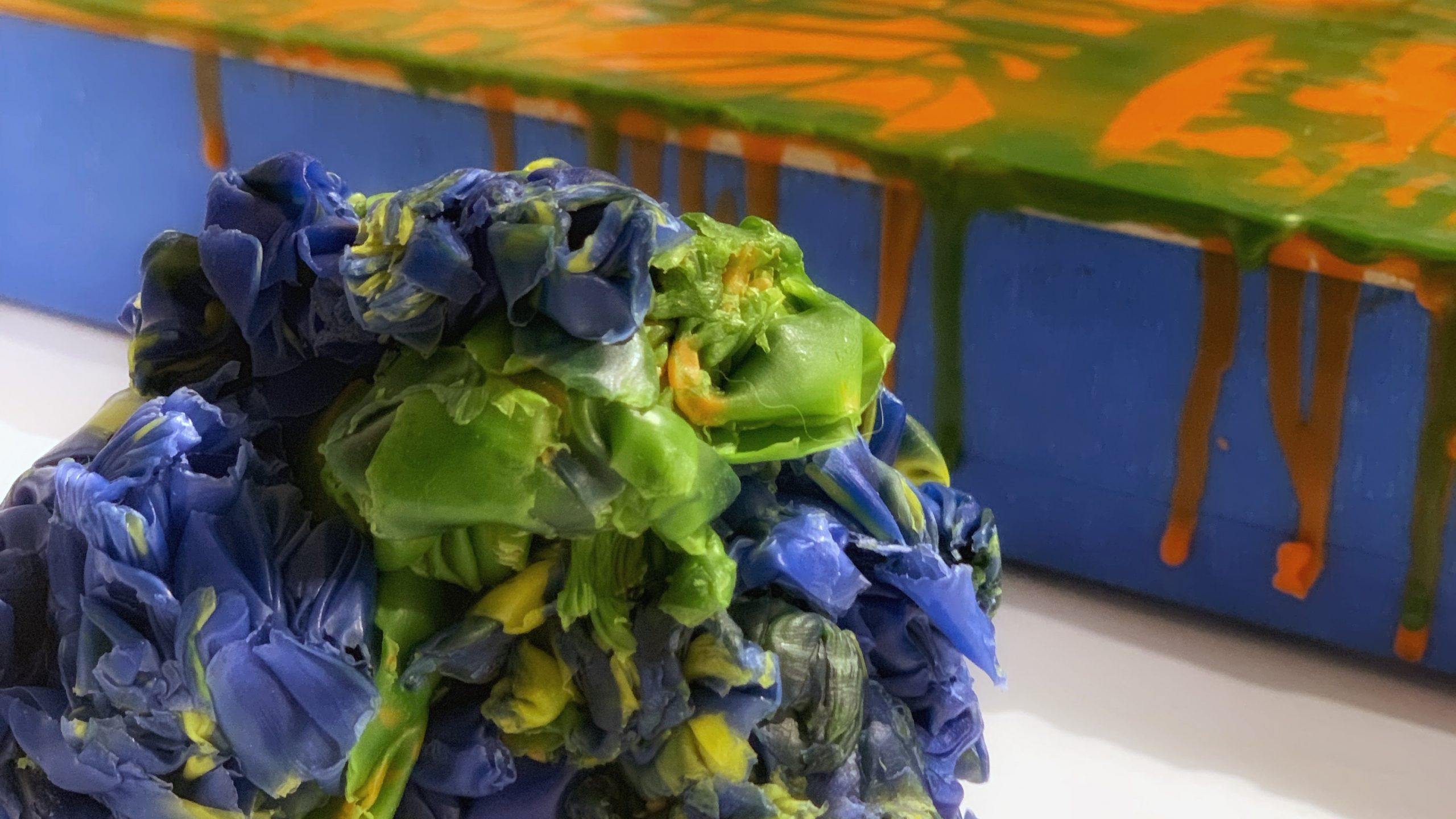 Close-up of a ball of wax scraping. There is an encaustic painting in the background that is laying flat on the same table as the wax ball. The colours in the ball are blue, green, and yellow. The colours in the painting are green and orange. The sides of the painting panel are tapped with blue painter's tape.